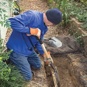 Man digging sewer drain in ground with shovel